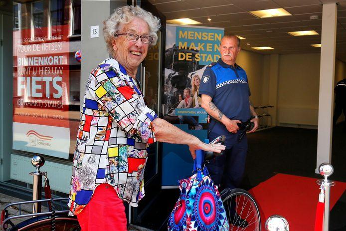 Jo Vierkant met haar fiets op de rode loper van de nieuwe bewaakte fietsenstalling.