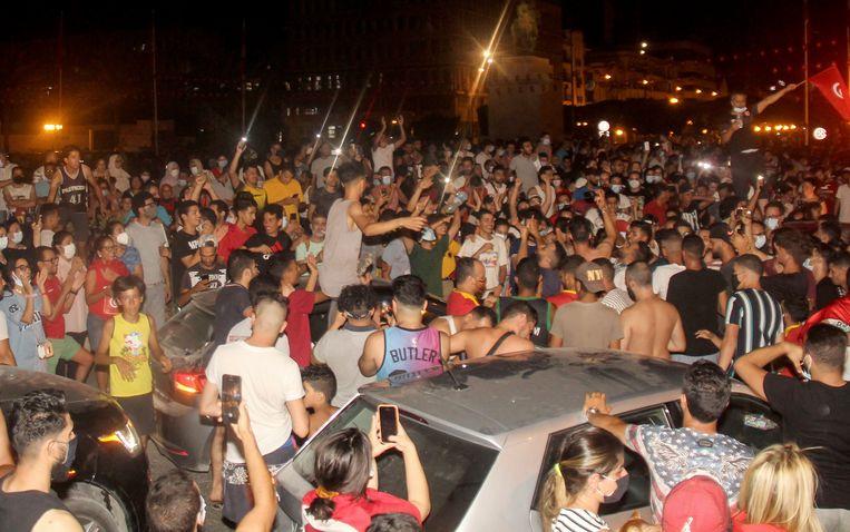Demonstranten vieren zondagavond het wegsturen van de de regering en het parlement door president Kais Saied in de Tunesische hoofdstad Tunis.  Beeld AP