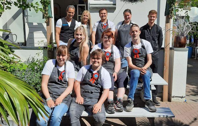 Eigenaren Ralph en Dianne de Nijs met hun personeel. Naast de mensen met een beperking bestaat het team uit keukenpersoneel en serveersters.