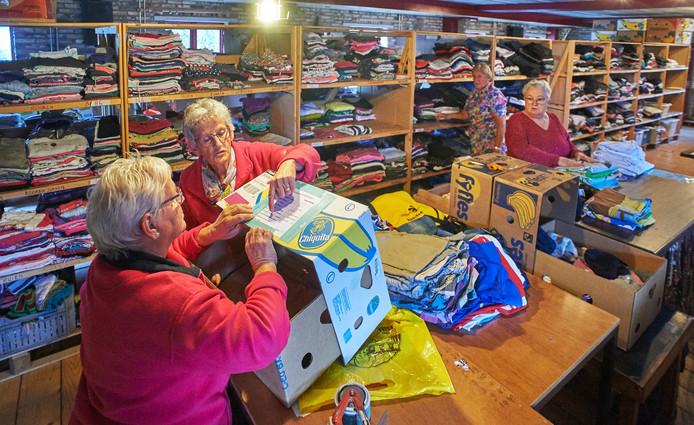 Vrijwilligers aan de slag in de schuren en stallen van Stal Swanenberg. Maria Hendriks (links) en Thea van Roosmalen stellen pakketten samen.