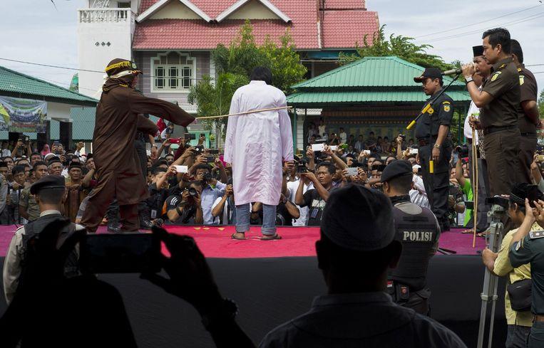 Een Indonesische Sharia politie-agent slaat een man tijdens een publieke stokslagen-ceremonie in Banda Aceh. Beeld afp