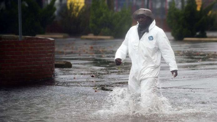 Een man loopt door een overstroomde straat in Maryland.