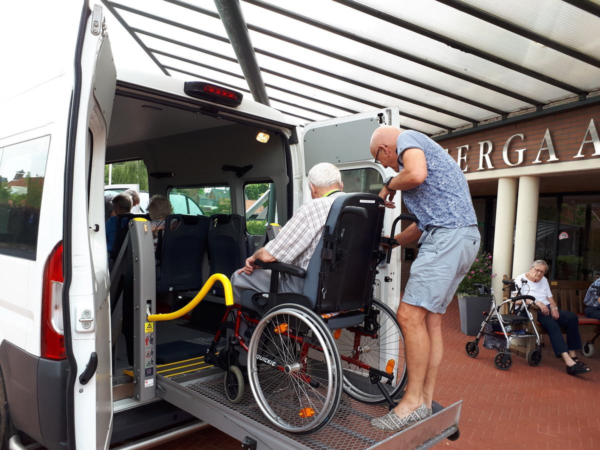 Een vrijwilliger helpt een reiziger de Noaberbus in. Het aantal vrijwillige chauffeurs is het afgelopen jaar vanwege corona bijna gehalveerd.