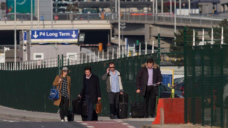 Passagiers verlaten de luchthaven van Zaventem na de aanslagen gisteren. Beeld AP