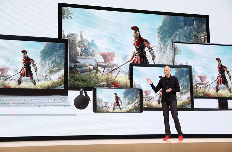 Stadia-baas Phil Harrison toont op het scherm hoe de game 'Assassin's Creed: Odyssey' op verscheidene schermen kan worden gespeeld. Beeld AFP