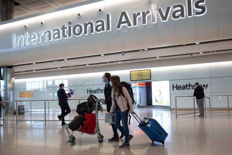 Reizigers in de aankomsthal van luchthaven Heathrow in het Verenigd Koninkrijk.  Beeld AP