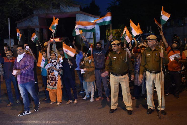 Demonstranten zwaaien met de Indiase vlag en politieagenten drommen samen voor de gevangenis van Tihar waar de verkrachters werden geëxecuteerd. Beeld AFP