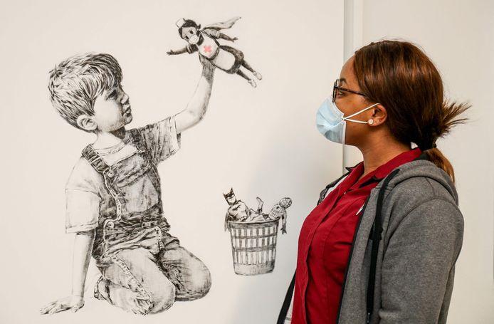 Een ziekenhuismedewerkster poseert met de tekening.