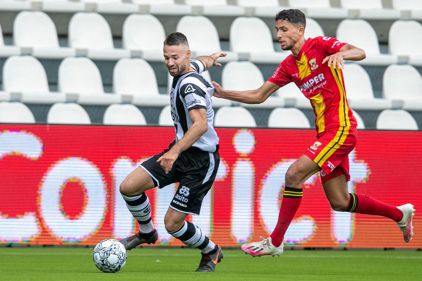 Heracles-speler Marco Rente wordt op de huid gezeten door Zakaria Eddahchouri van Go Ahead Eagles.
