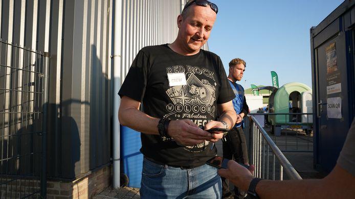 Eerst even de coronacheck doen, Iwan de Visser controleert hier de QR code van een bezoeker die op het festivalterrein van Kaaipop in Breskens wil komen.