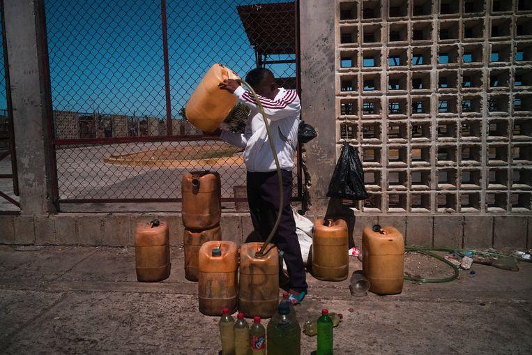 Een man probeert aan een busstop in Paraguaipoa benzine te verkopen. Beeld NYT/ADRIANA LOUREIRO FERNANDEZ