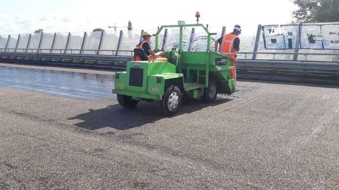 Op een kleeflaag wordt steenslag aangebracht zodat het asfalt straks beter hecht aan het beton.