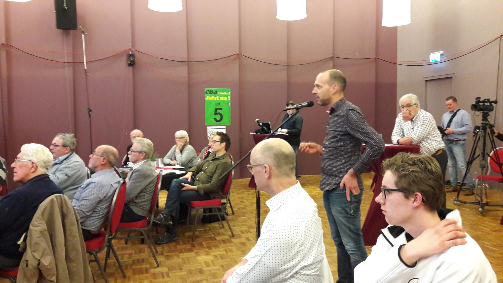 Joep Manders uit Schaijk vuurt een vraag af op het panel van lijsttrekkers op het podium.