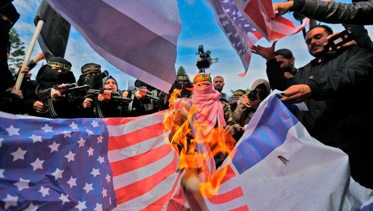Aanhangers van de Palestijnse groep Islamic Jihad verbranden Amerikaanse vlaggen tijdens een protest in Gaza tegen het besluit van de Amerikaanse president Donald Trump om Jeruzalem te erkennen als hoofdstad van Israël. Beeld afp