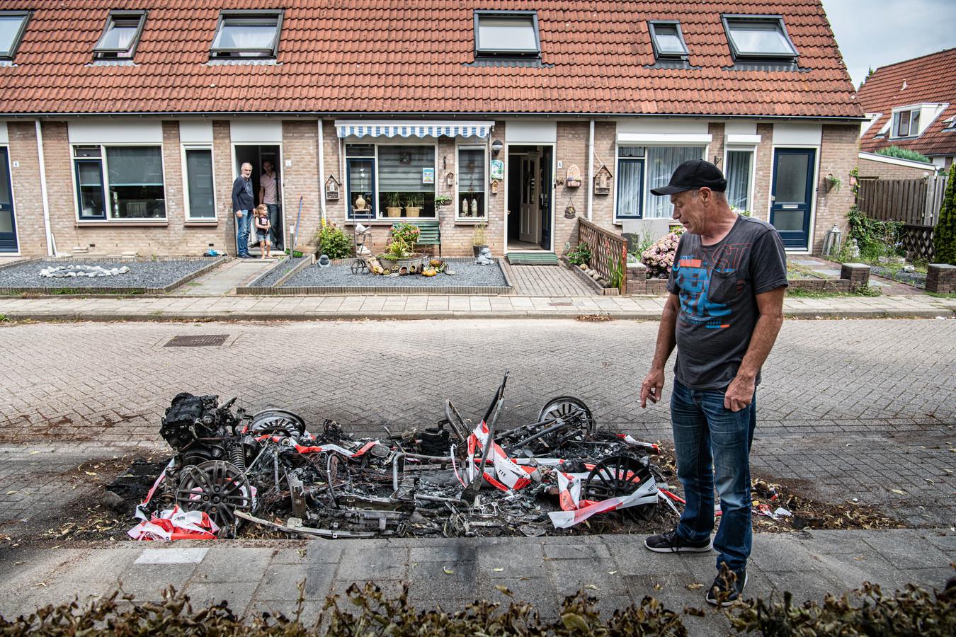 Wim Theunissen uit Beuningen bij wat eerder zijn auto was. Door vermoedelijke brandstichting is er slechts nog wat ijzer over. De rest is weggesmolten.