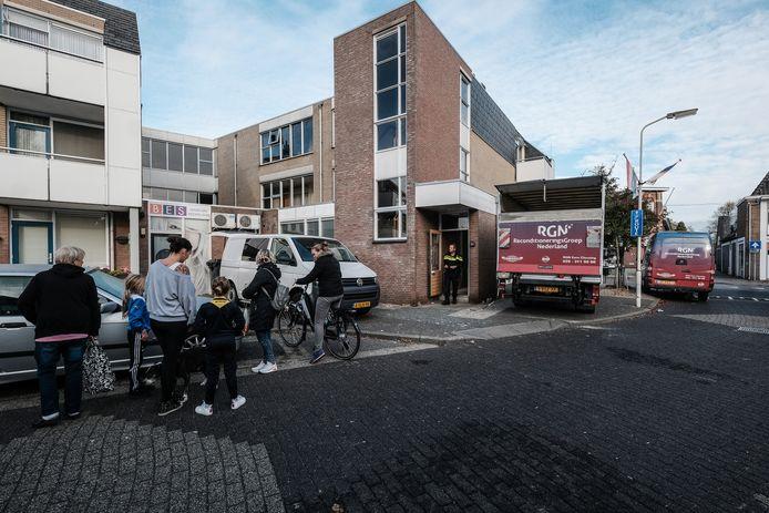 Mensen bekijken de activiteiten bij het onderzoek van de politie naar de brand in het appartement in De Ent.