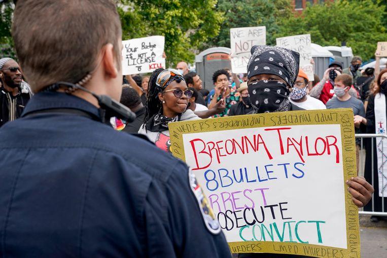 Een demonstrant confronteert een politieagent tijdens een protest in  Louisville, Kentucky, na de dood van Breonna Taylor. Beeld REUTERS
