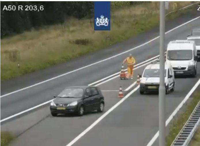 Op deze videostill van Rijkswaterstaat is te zien dat en auto nog over het verdrijvingsvlak rijdt terwijl de mederwerker bezig is met pionnen neerzetten.