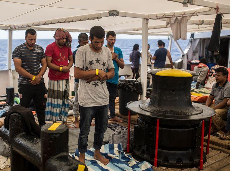 Migranten bidden aan boord van het hulpschip Open Arms, na hun redding uit een rubberboot. Beeld AP