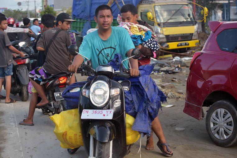 Inwoners van Palu met geplunderde goederen. Beeld AFP