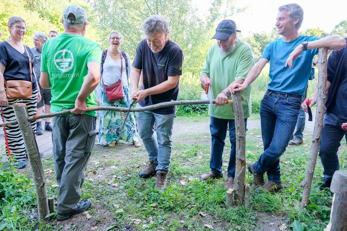In plaats van een lint door te knippen, werd er een stok doorgezaagd als officiële opening van het wandelpad.