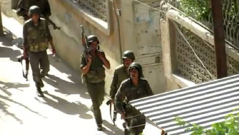 Syrische soldaten lopen gewapend over straat in Damascus. Beeld afp