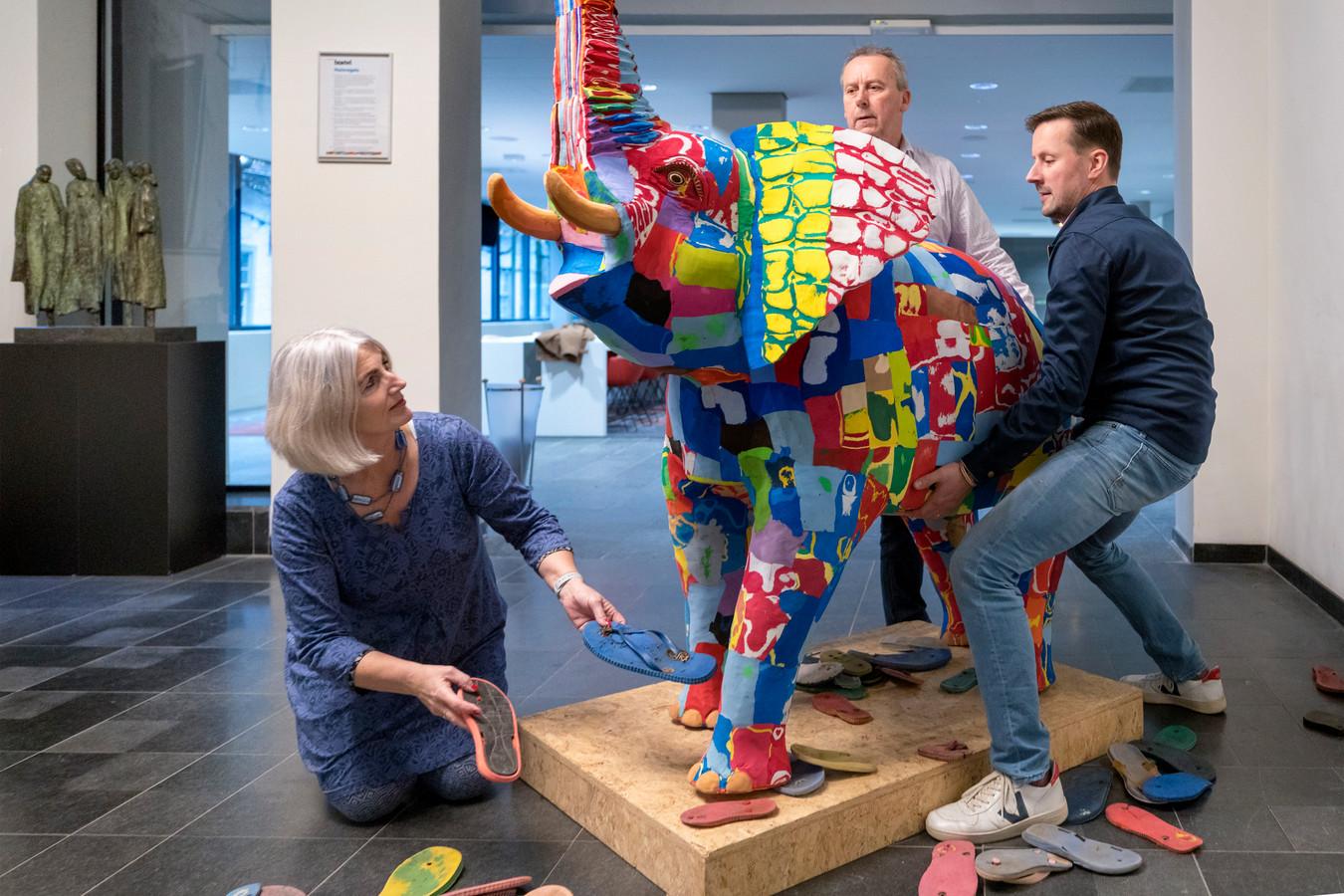 De nieuwe aanwinst in het gemeentehuis, een kunstzinnige olifant van afgedankte plastic slippers gemaakt, is vanmiddag op zijn plaats gezet door wethouder Marusjka Lestrade, wethouder Herman van Wanrooij en Nicholas Ninaber van Eijben (rechts).