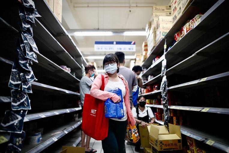 Lege schappen in een supermarkt in Taipei. In Taiwan zijn strengere lockdonwmaatregelen ingesteld. Beeld EPA