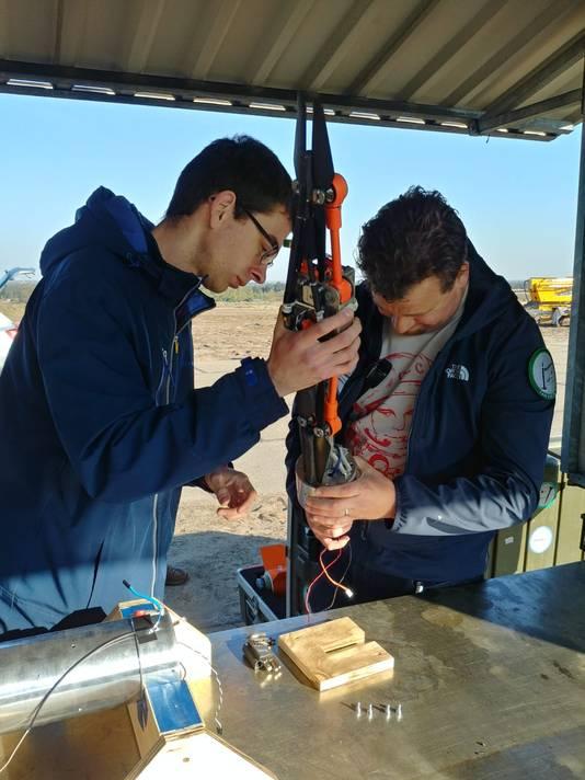 Medewerkers van Delft Dynamics doen de drone in een koker die even later met een raket wordt gelanceerd.