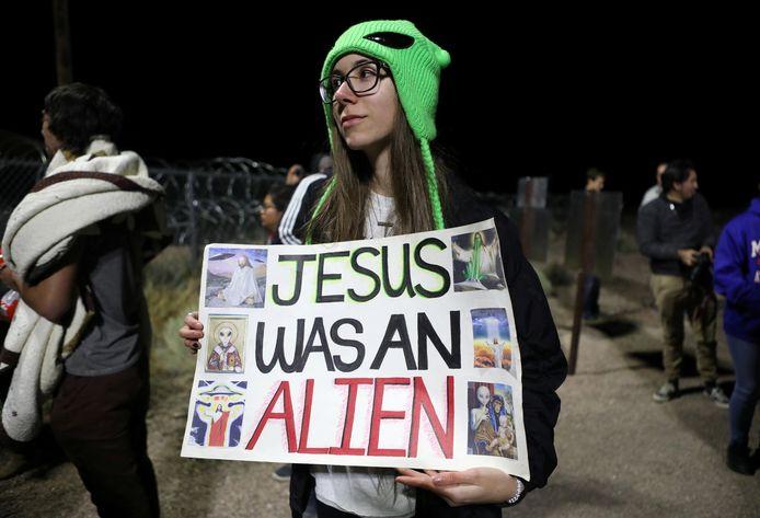 Een vrouw met een bordje 'Jezus was een alien' staat voor de ingang van Area 51, een geheim militair complex in de Nevada-woestijn waar volgens 'believers' ufo's worden nagebouwd en misschien zelfs de overblijfselen liggen van aliens die in 1947 zouden zijn neergestort.