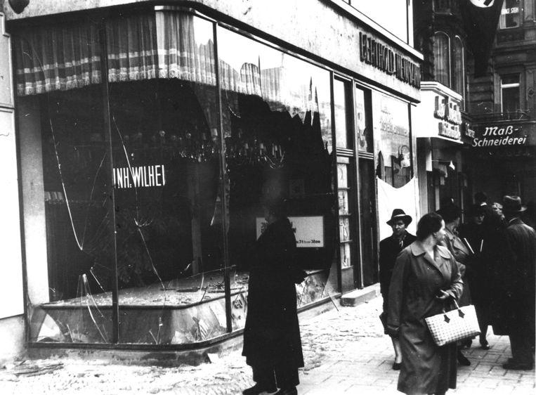 Duitse burgers lopen op 10 november 1938 langs de kapotte etalageuit van een joodse winkelier, nadat de zogeheten Kristallnacht had plaatsgevonden. Beeld Hollandse Hoogte /  ANP