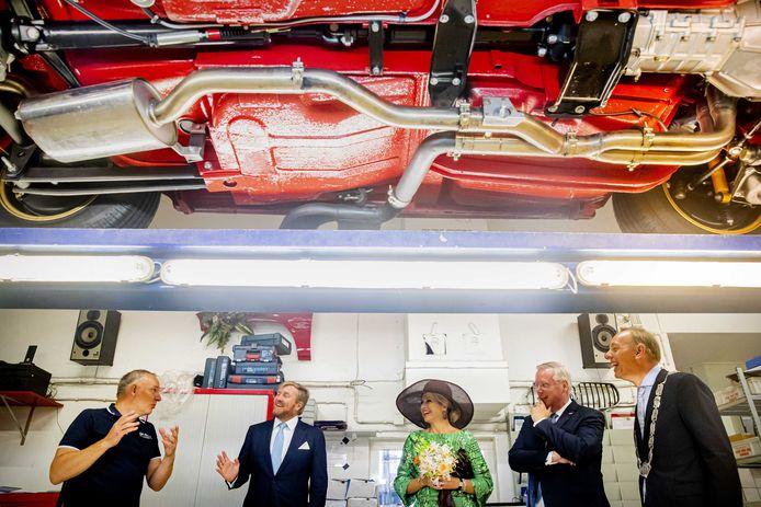 Jan Nijland (links) geeft terwijl een auto in zijn garage op de brug staat uitleg aan Willem-Alexander en Maxima. Rechts Commissaris van de Koning Andries Heidema en Deventer burgemeester Ron König.