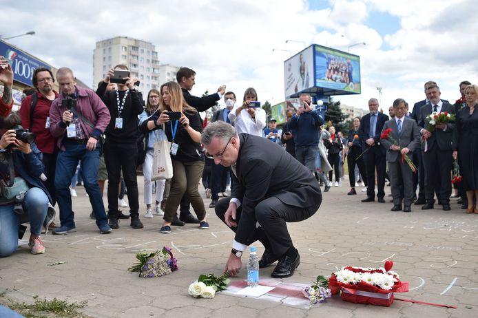 Het hoofd van de delegatie van de Europese Unie in Wit-Rusland legt bloemen neer op de plek waar een betoger omkwam.