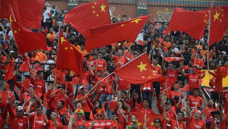 Chinese fans zwaaien met vlaggen tijdens een kwalificatiewedstrijd van het nationale team voor het WK 2018. Beeld afp