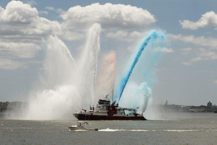 Blusboten van de brandweer spuiten gekleurd water in de haven van New York.