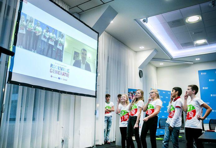 Basisschoolleerlingen kijken naar de video die zij hebben opgenomen voor staatssecretaris Blokhuis van Volksgezondheid.