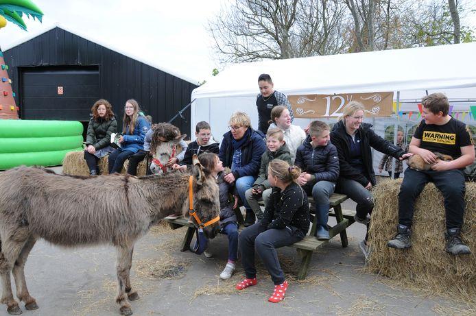 Astrid Boot (met sjaal) te midden van 'haar kinderen' bij zorgboerderij Aan de Hand. Het christelijk begeleidingscentrum in Brijdorpe vierde vorige week het 12,5-jarig bestaan.