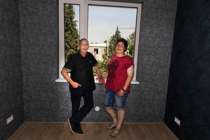 Chris en Sandy van Rooij zijn al klaar met het behangen van de slaapkamers in hun nieuwe woning. Op de achtergrond de wisselwoning waar ze tijdelijk verblijven.