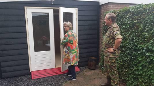 Coördinator Barbara van der Meulen opent het nieuwe huisje. Kolonel Burg Valk kijkt toe.