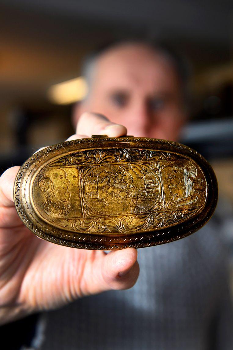 Stadsarcheoloog Piet Kleij toont een protestantse spotprent op een tabaksdoos deksel in het archeologisch depot in Zaandijk.  Beeld Olaf Kraak