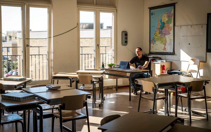 Leerkracht Paul Rentmeester geeft onderwijs op afstand aan zijn leerlingen in een leeg klaslokaal op 't Palet in Eindhoven.