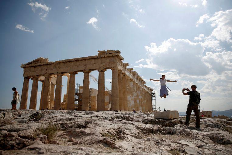 Toeristen maken foto's bij het Parthenon, de tempel voor Athena Parthenos, die de beschermgodin van de stad Athene was. Beeld Reuters