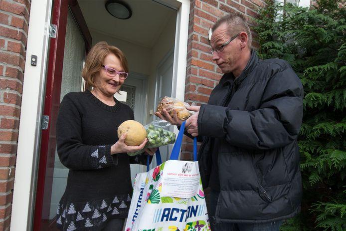 Sonja Thys krijgt door Patrick Eliveld een tas met levensmiddelen thuisbezorgd.
