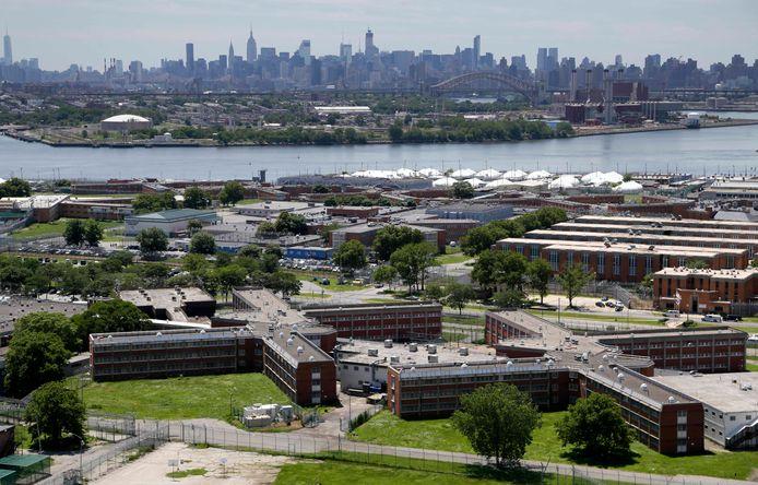 Het Rikers Island gevangeniscomplex in New York vanuit de lucht, met op de achtergrond de skyline van Manhattan.