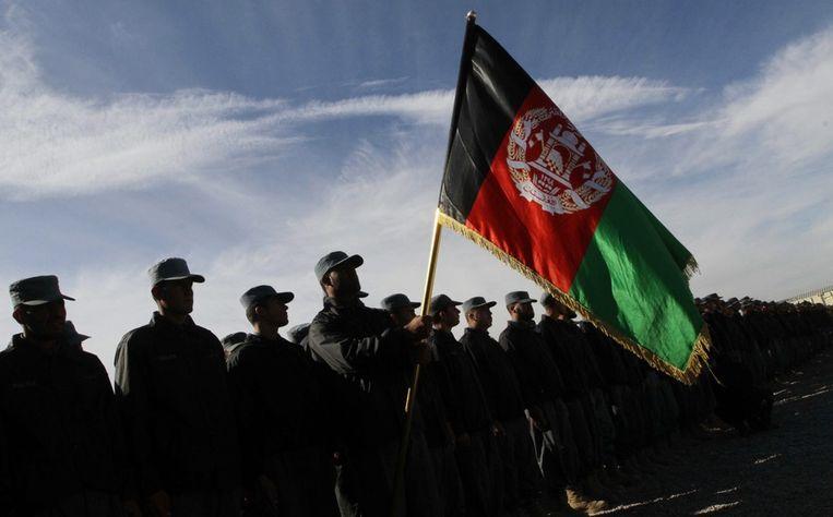 Afghaanse Agenten houden de Afghaanse vlag omhoog tijdens de ceremonie voor het afstuderen van de agenten. Beeld epa