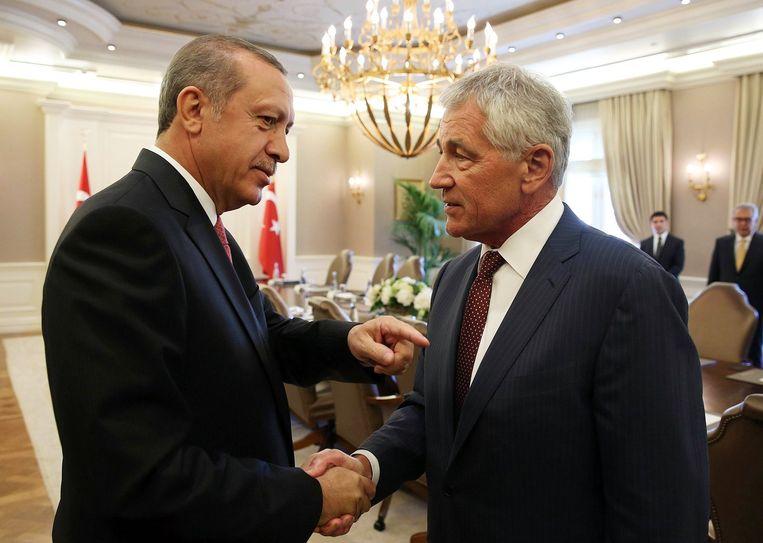 De Turkse president Erdogan (links) schudt de hand van de Amerikaanse minister van Buitenlandse Zaken, Chuck Hagel. De twee hadden deze week een ontmoeting om te praten over actie tegen IS. Beeld afp