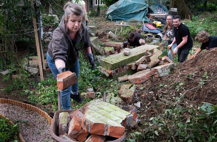 Inwoners uit alle hoeken van Leersum zetten gezamenlijk de schouders eronder om het puin dat de storm heeft achtergelaten, op te ruimen.