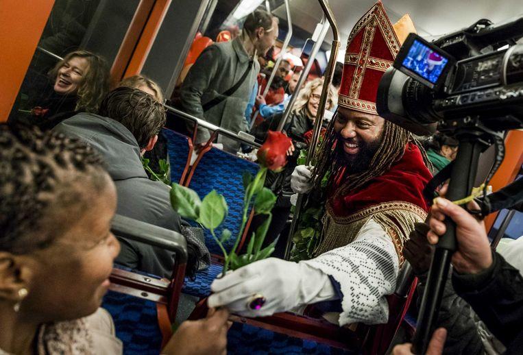 2016-11-05 11:53:21 AMSTERDAM - De Nieuwe Sint (Patrick Mathurin) deelt rozen uit aan reizigers in een metro tijdens zijn intocht in Amsterdam. ANP REMKO DE WAAL Beeld anp