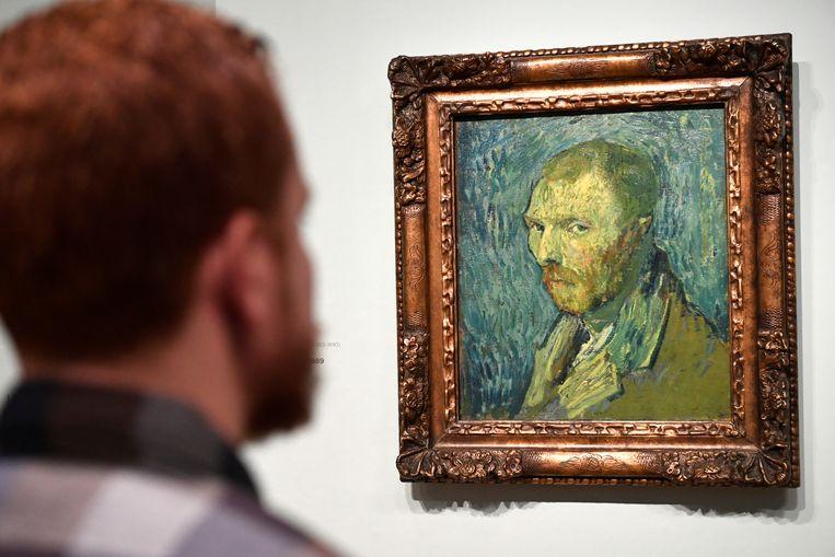 Een man kijkt naar 'Zelfportret' (1889) van Vincent Van Gogh. Beeld REUTERS