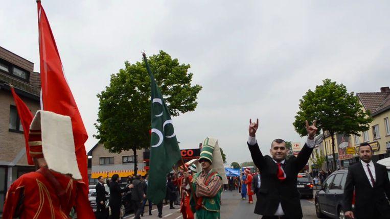 Een deelnemer aan de optocht in Heusden-Zolder maakt het Grijze Wolven-gebaar Beeld rv